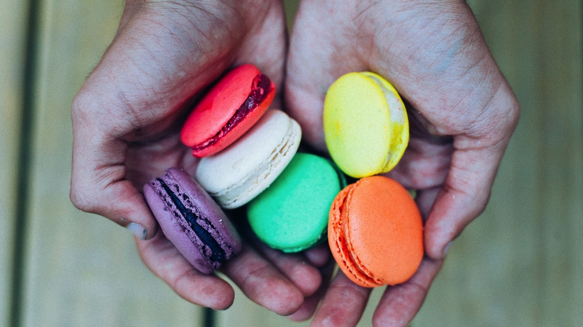 Close-up of hands holding colorful macaroons