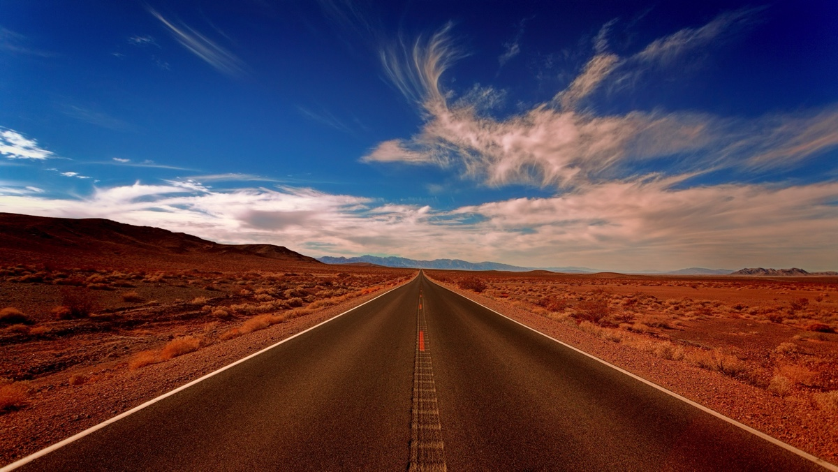 Long road in a desert and blue skies