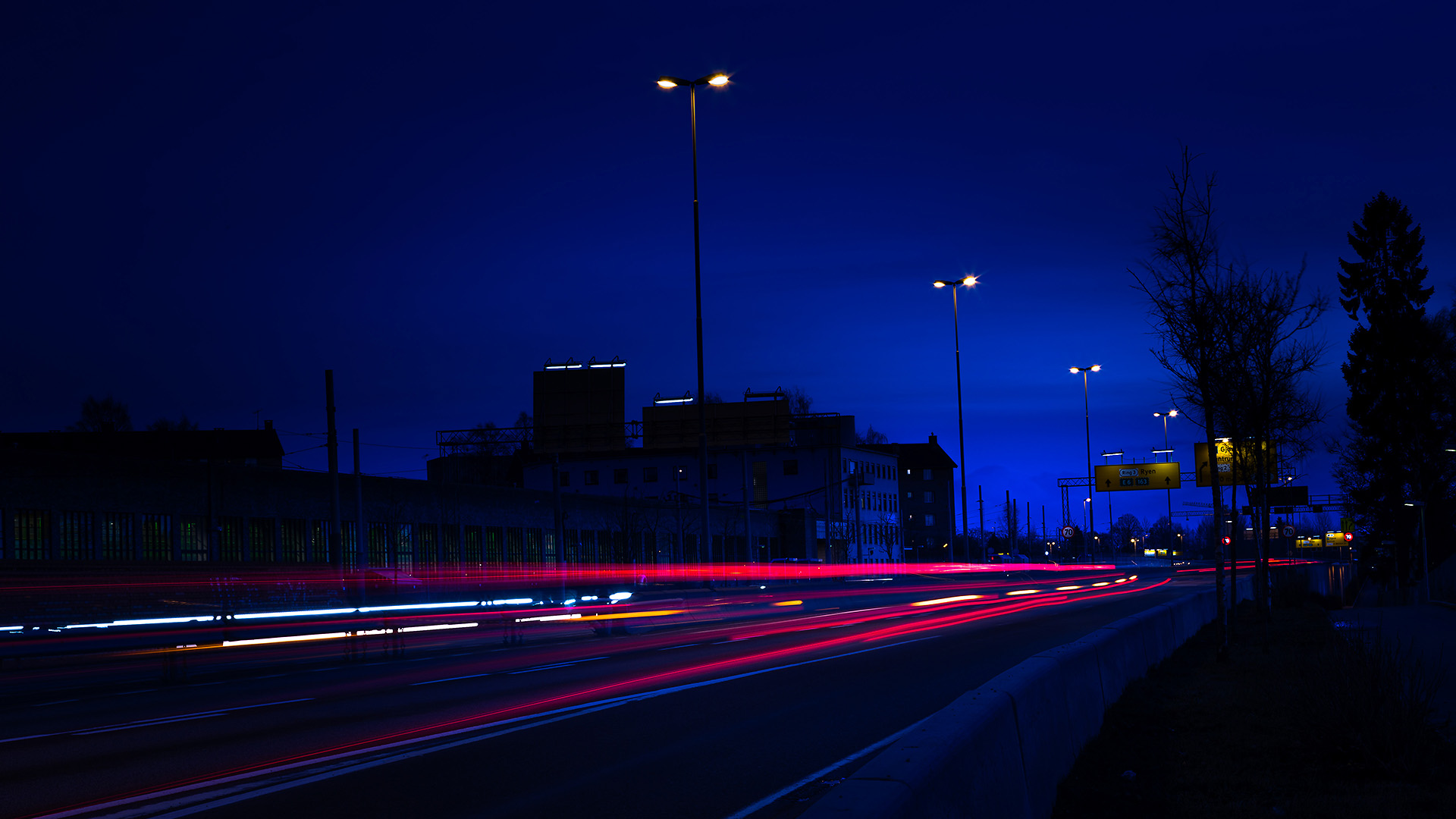 A darkly lit image of a highway. Streaks of head and red tail lights can be seen in the lower part of the frame. In the distance are silhouettes of buildings, road lights and signs.