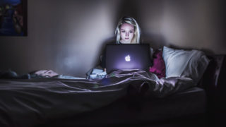 Woman in front of laptop in dark room - tracked by search engines.